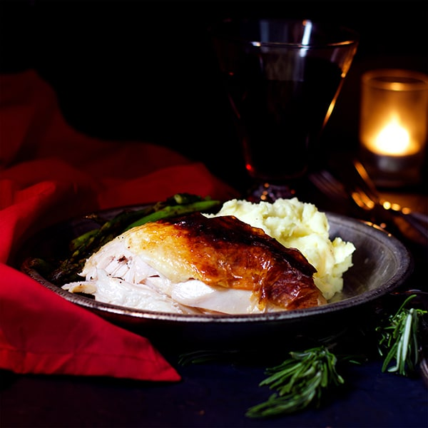 A plate with buttermilk roast chicken, mashed potatoes, and green beans