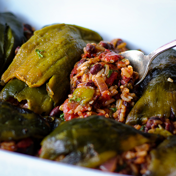 Filling roasted poblano peppers with a rice, beans, tomato, and enchilada sauce.