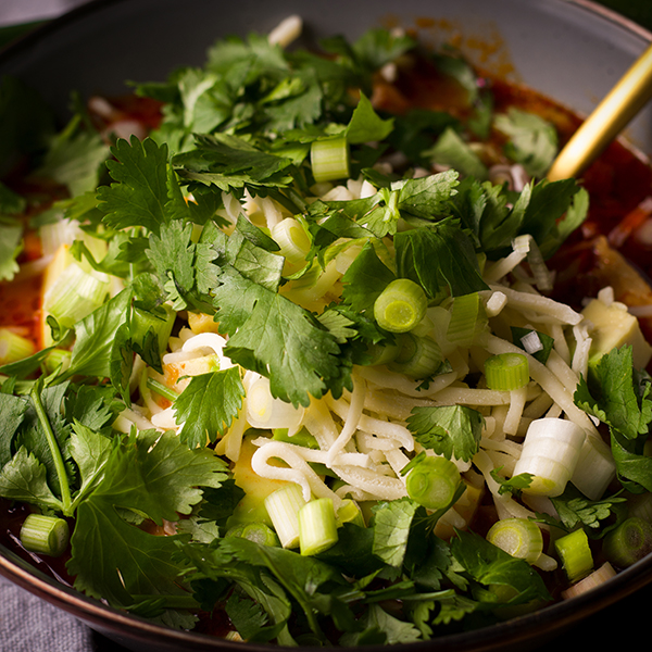 A bowl of chicken tortilla soup topped with cheese, cilantro and green onions.