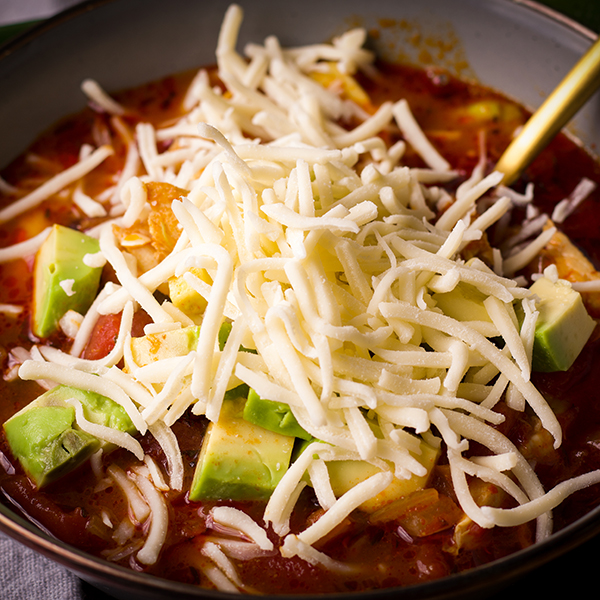 A bowl of chicken tortilla soup with shredded cheese and avocados.