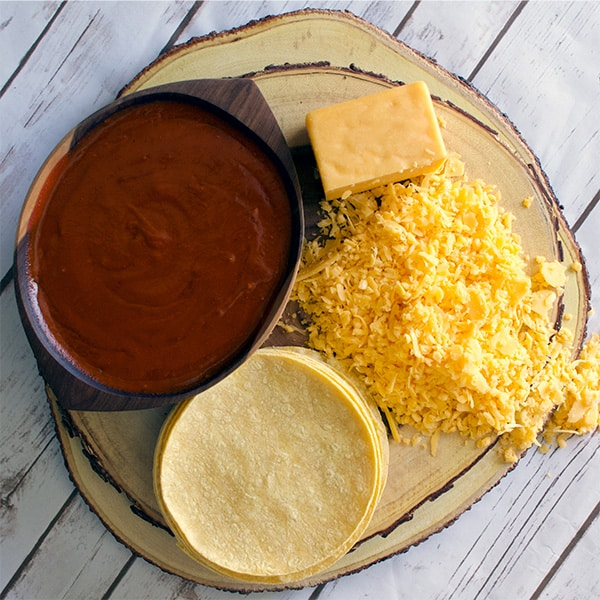 Ingredients to make cheese enchilada casserole: homemade red chili enchilada sauce, shredded cheese, and corn tortillas.