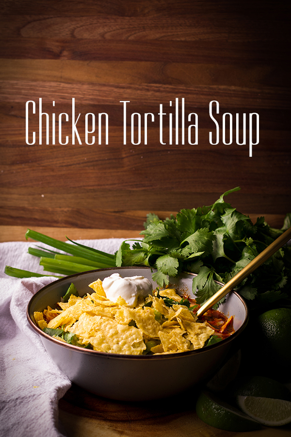 A bowl of chicken tortilla soup topped with crushed tortilla chips and sour cream.