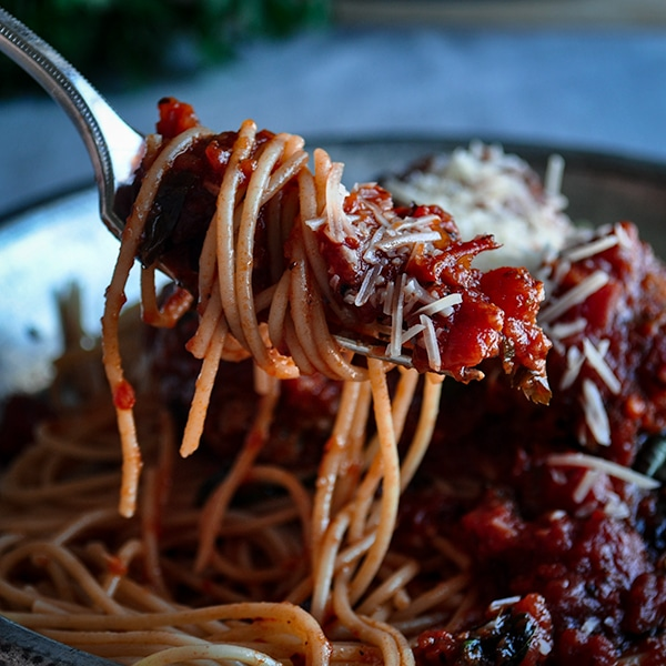 Taking a bite of spaghetti with homemade meatballs and marinara.
