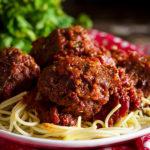 A plate of spaghetti and meatballs in marinara sauce.