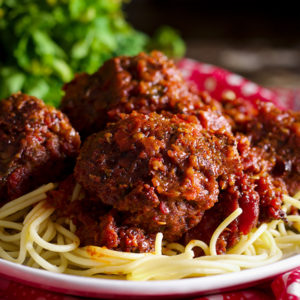 A plate of spaghetti and meatballs in marinara sauce.