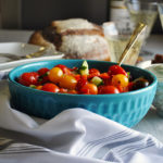 A bowl of tomato cucumber salad with basil whipped ricotta.