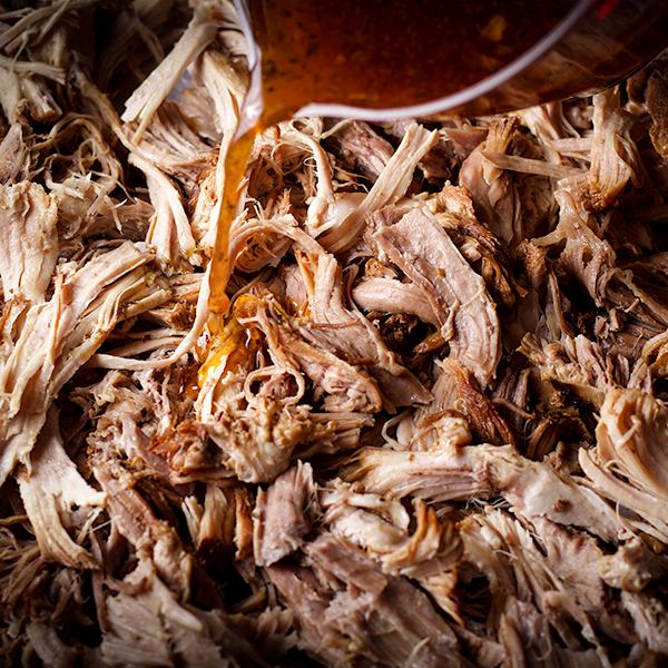 Pouring the flavorful cooking liquid over a tray of pork carnitas before putting the carnitas in the oven to crisp.