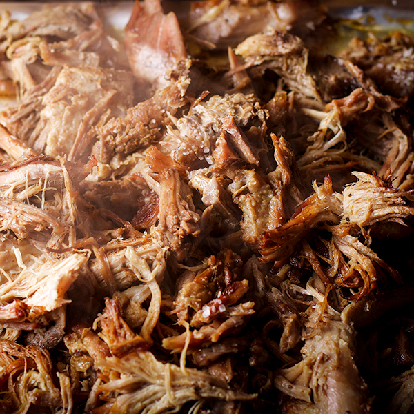 Pork Carnitas on a tray, hot from the oven with steam rising from them.
