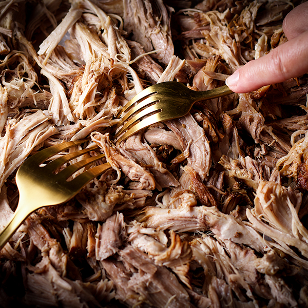 Someone using two forks to shred cooked pork roast into pieces to make Carnitas.