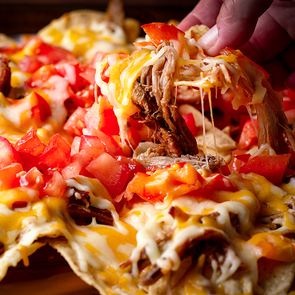 Someone lifting up a chip covered in cheese, carnitas, and fresh tomatoes from a tray of nachos.