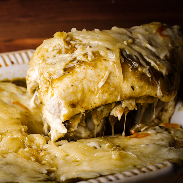 Lifting a serving of Chicken Enchiladas Verdes from the pan to serve it.