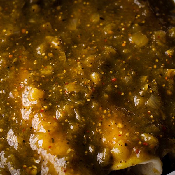 A pan of Chicken Enchiladas Verdes covered in Salsa Verde.
