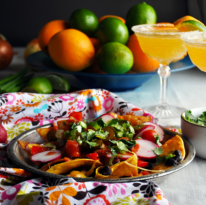 A plate of veggie black bean nachos with orange margaritas.