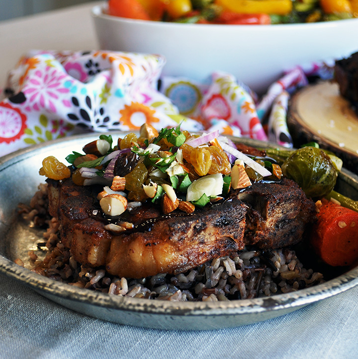 A plate of cider braised pork chops with rice, roasted vegetables, and agrodolche.