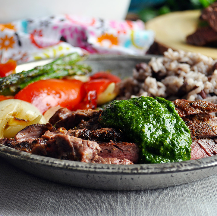 A plate with grilled flank steak and chimichurri sauce, rice and beans, and sautéed vegetables.
