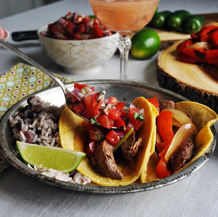 Spooning Pico de Gallo over flank steak tacos.