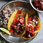 A plate of flank steak tacos topped with homemade Pico de Gallo