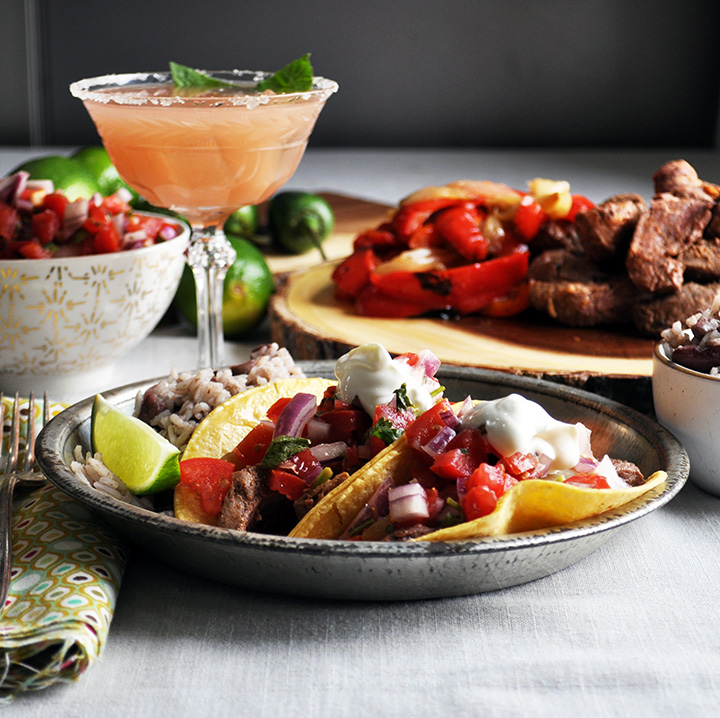 A plate of flank steak tacos topped with homemade Pico de Gallo and sour cream.