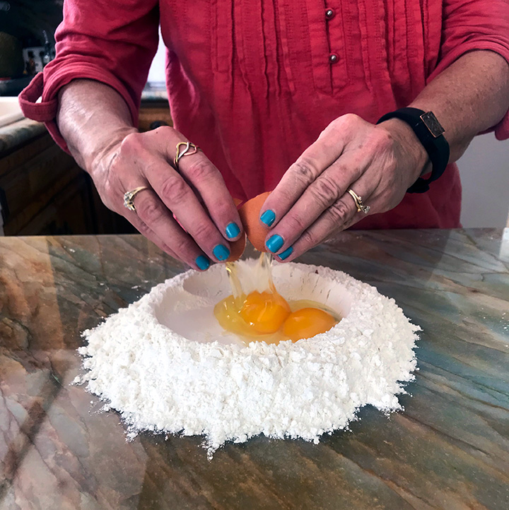 Cracking eggs into flour to make fresh homemade pasta dough