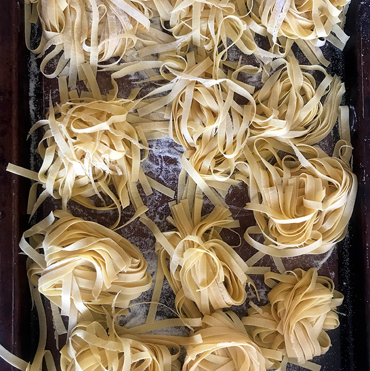 Piles of homemade pasta on a baking sheet, ready to cook.