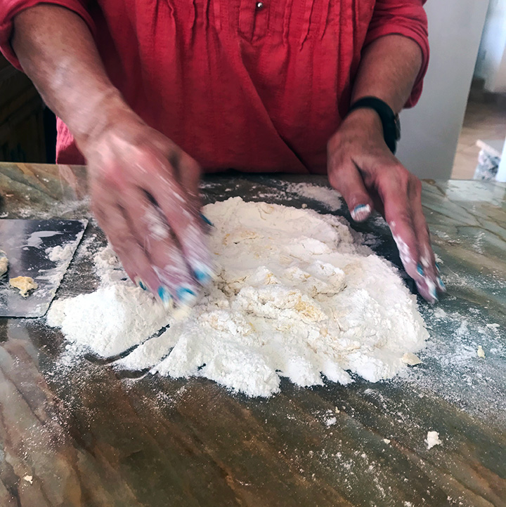 Mixing the eggs into flour to make fresh homemade pasta.