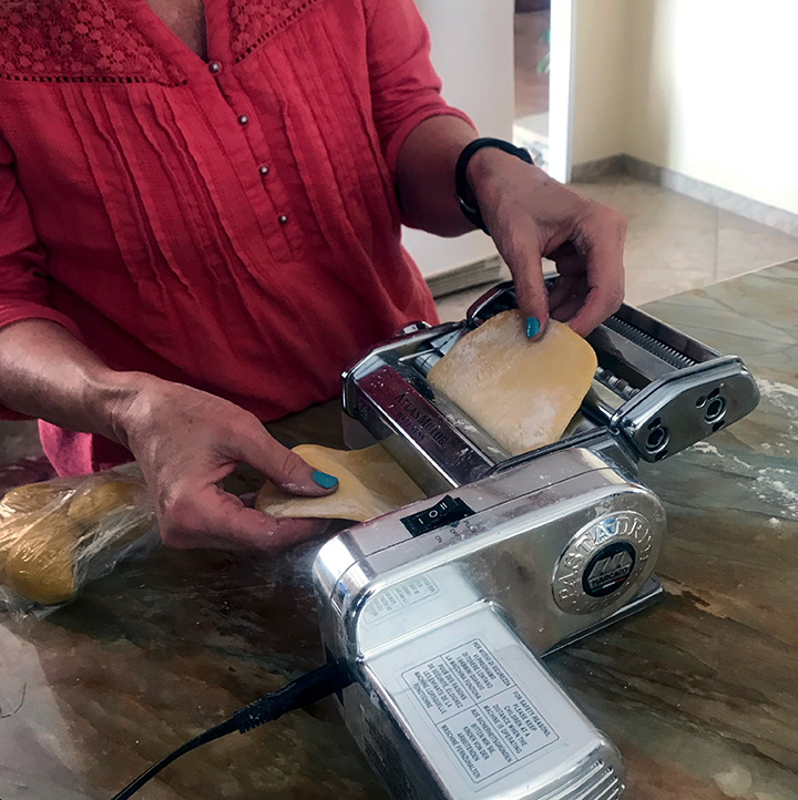 Putting pasta dough through a pasta machine.