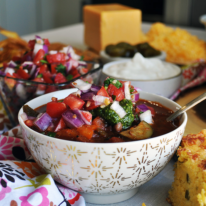 A bowl of vegetarian chili topped with Pico de Gallo and chimichurri sauce