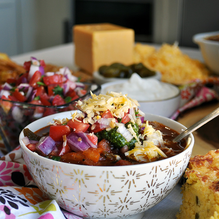 A bowl of vegetarian chili topped with Pico de Gallo and chimichurri sauce and cheese.