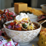 A bowl of vegetarian chili topped with Pico de Gallo, chimichurri sauce, cheese, and sour cream.