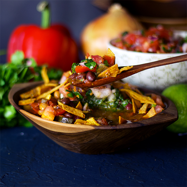 Taking a bite of vegetarian chili with pico de Gallo and fried tortilla strips.