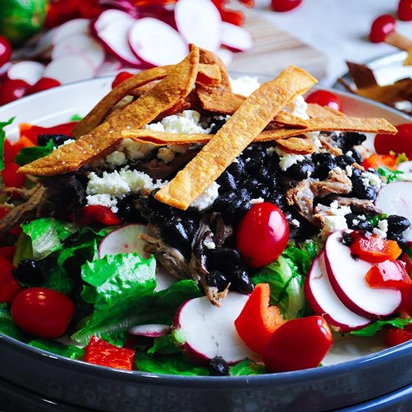 A big plate of taco salad with pork carnitas.