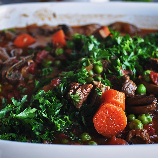 Vegetable beef soup topped with fresh parsley.
