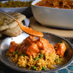 Spooning sauce over a plate of Indian Butter Chicken and Indian Rice.