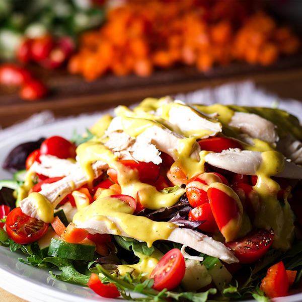 A plate of roast chicken salad with mango dressing.