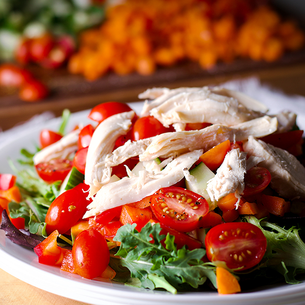 A plate of salad greens and chopped vegetables with roasted shredded chicken on top.