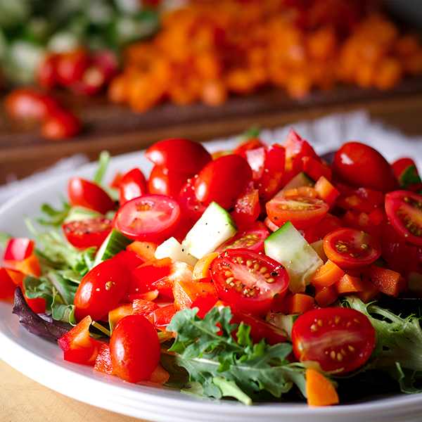 A plate of salad greens and chopped vegetables.