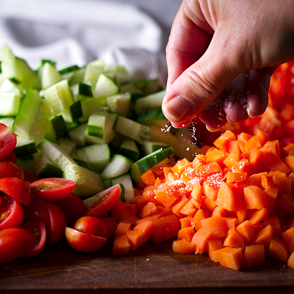 Sprinkling salt over chopped tomatoes, cucumbers, carrots, and red bell peppers.