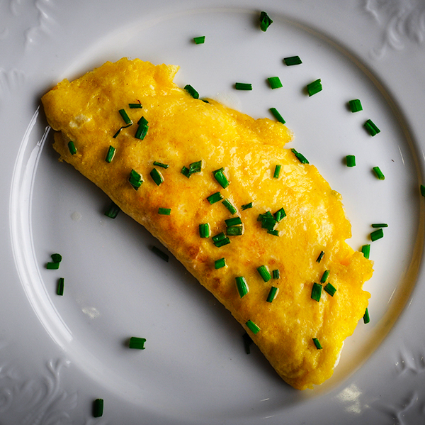 A French omelette filled with Boursin cheese on a plate, ready to eat.