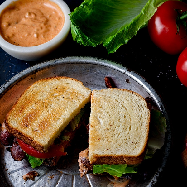 A BLT sandwich on a plate, cut in half.