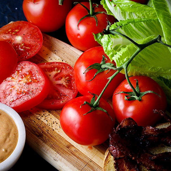 Tomatoes, lettuce, bacon, and special sauce for BLT sandwiches.