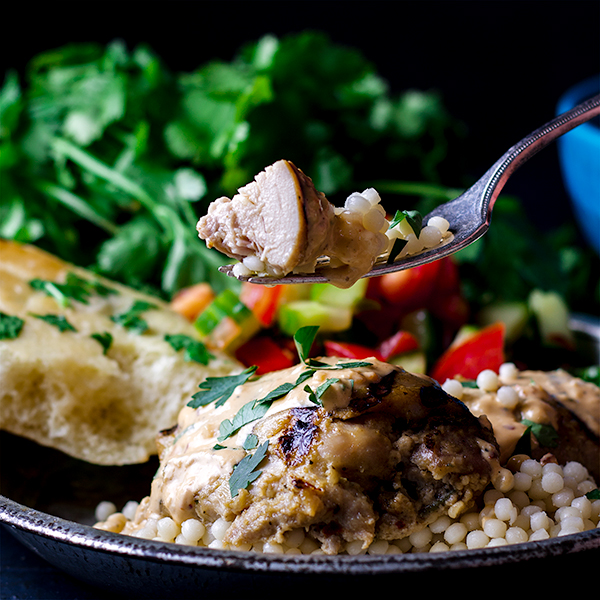 Taking a bite of tahini grilled chicken with couscous.