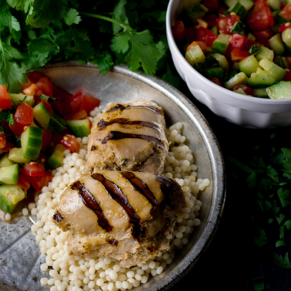 Tahini Grilled Chicken with Couscous on a plate with tomato and cucumber salad.