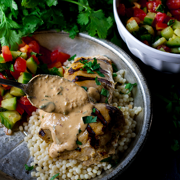 Spooning tahini yogurt sauce over tahini marinated chicken and couscous.