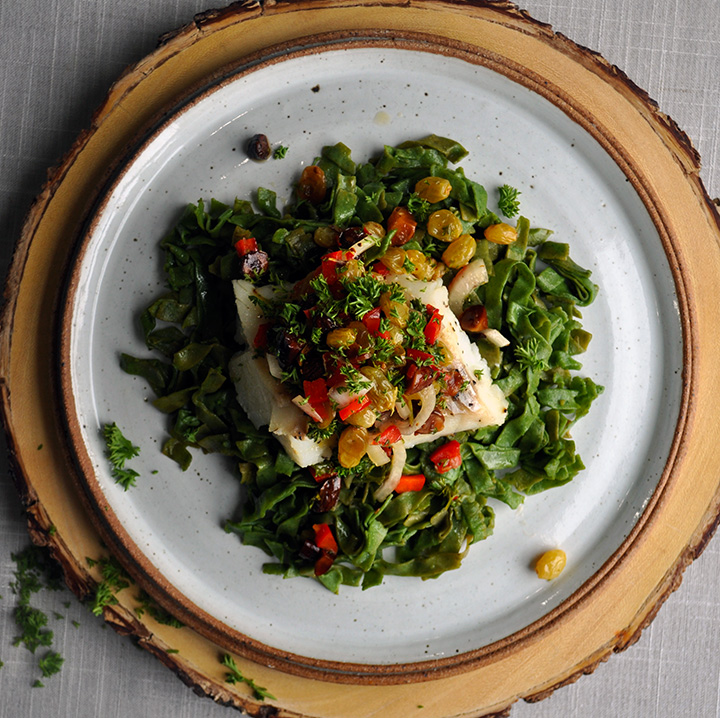 A plate of spinach pasta with baked cod and agrodolce