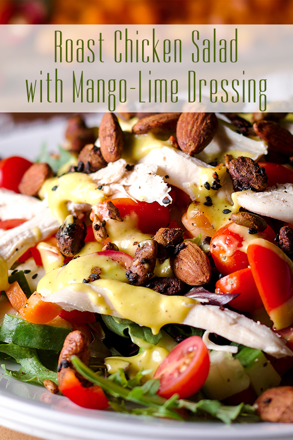 A plate of roast chicken salad with mango dressing and roasted nuts.