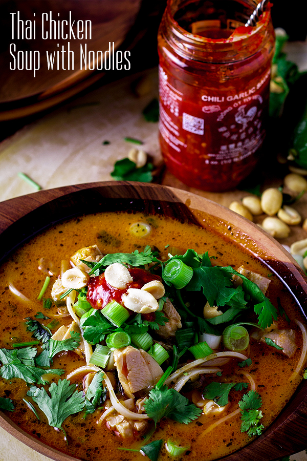 Thai Chicken Noodle Soup topped with peanuts, cilantro, and chili garlic sauce