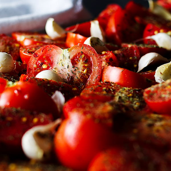 A tray of tomatoes and garlic ready to be roasted for Roasted Tomato Sauce.