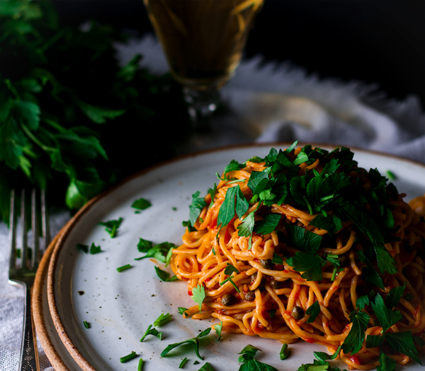 A plate of Spaghetti Puttanesca topped with parsley.