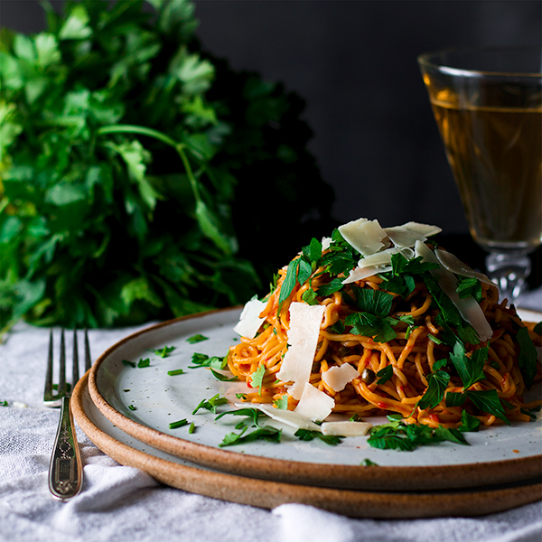 A plate of Spaghetti Puttanesca topped with parsley and shaved parmesan.