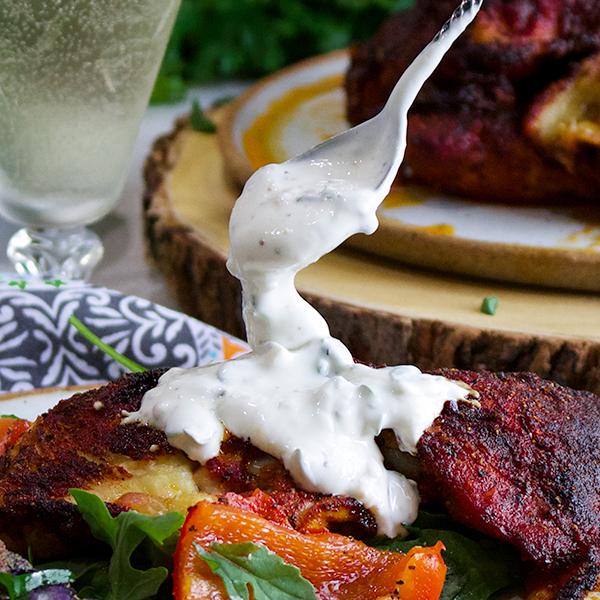 Spooning herbed yogurt sauce over paprika chicken.